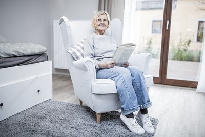 Woman sitting in armchair with magazine