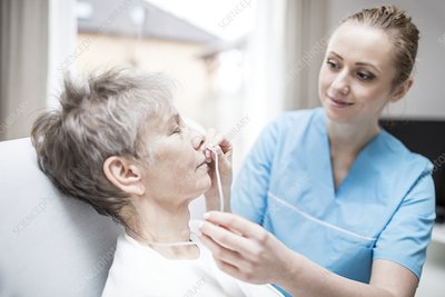 Carer inserting nasal cannula in patient