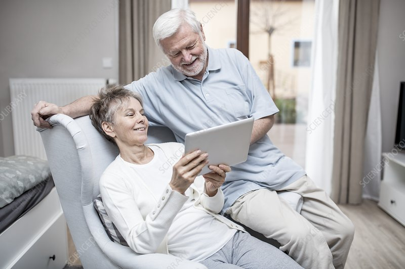 Senior couple in hospital room with tablet
