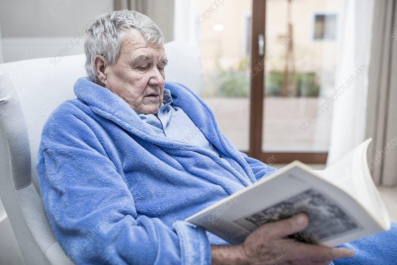 Senior man reading magazine