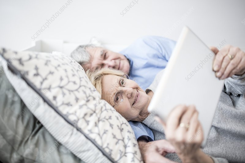 Senior couple lying down watching tablet