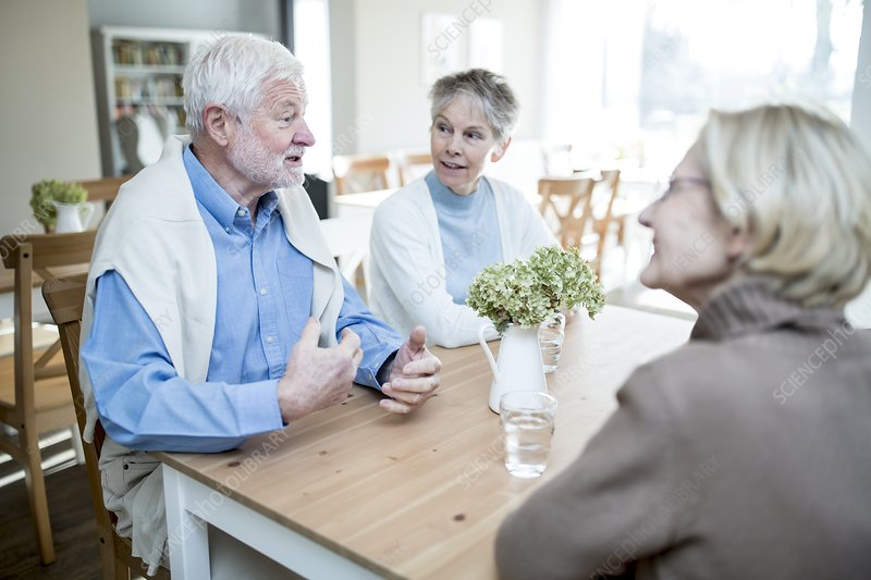 Senior man talking to two female friends