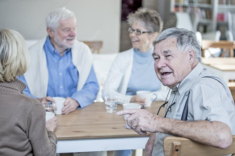 Friends talking and smiling in retirement home