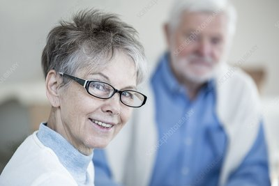 Woman in glasses smiling towards camera