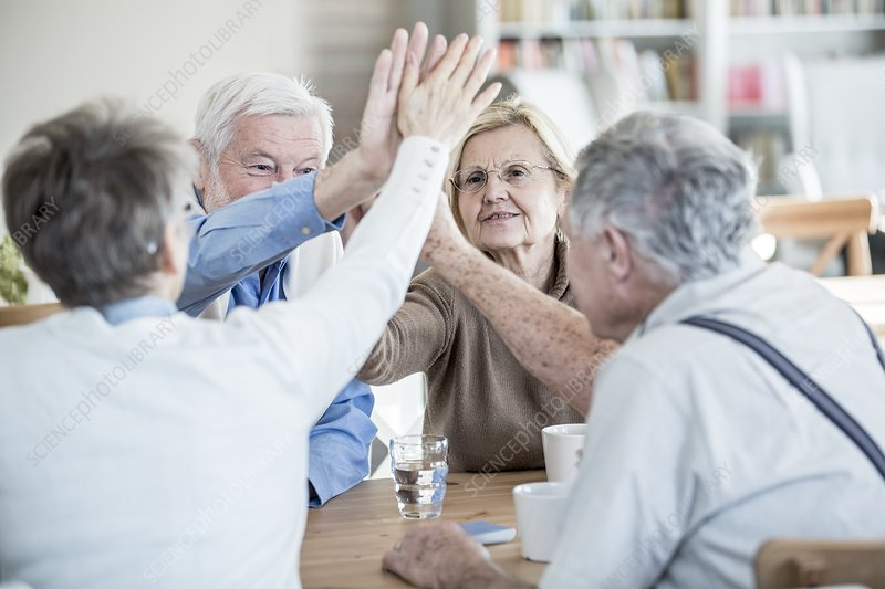 Friends giving high fives in retirement home