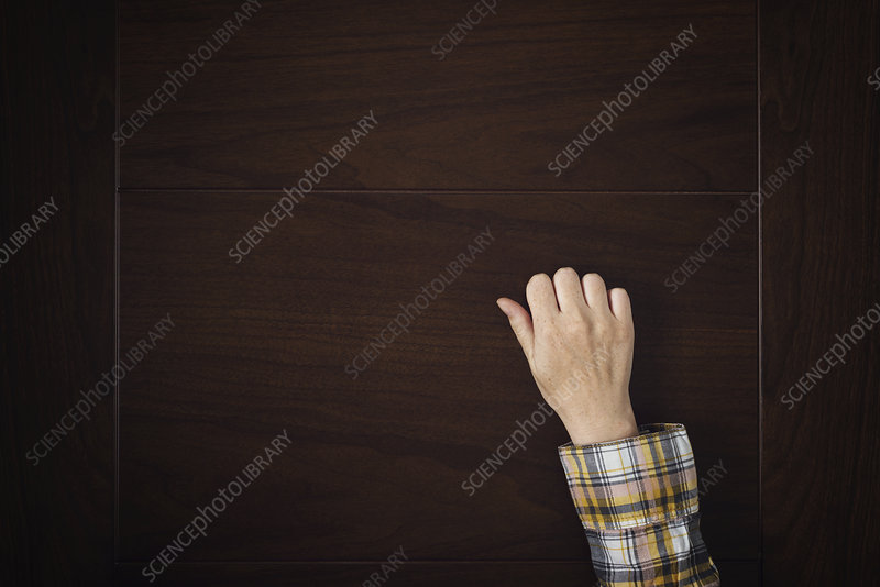 Hand knocking on a door