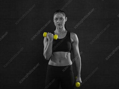 Woman holding yellow hand weights