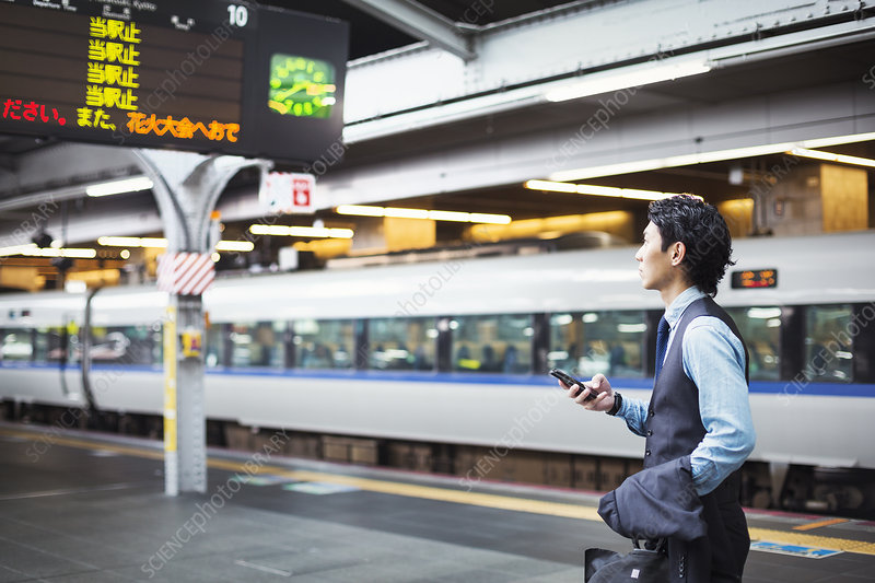 Businessman on train station platform, holding mobile phone