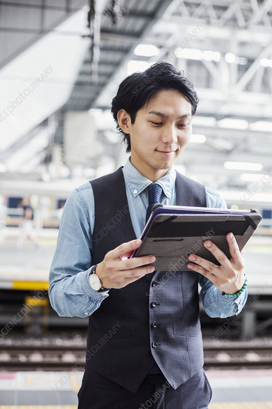 Businessman holding digital tablet, train station platform