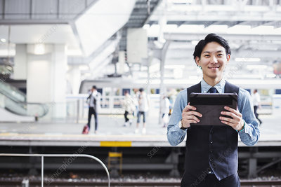 Businessman, train platform, digital tablet