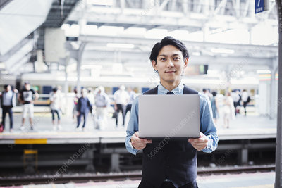 Businessman, train platform, laptop, looking at camera