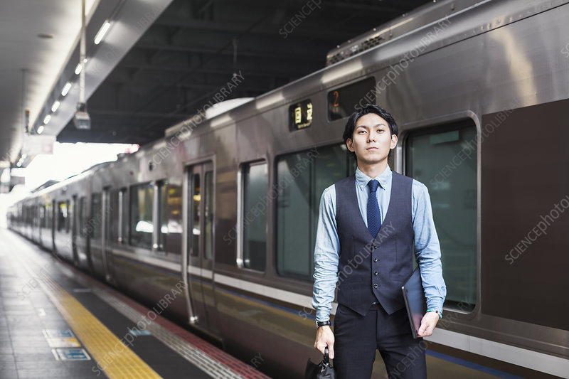 Businessman, train platform, digital tablet, briefcase