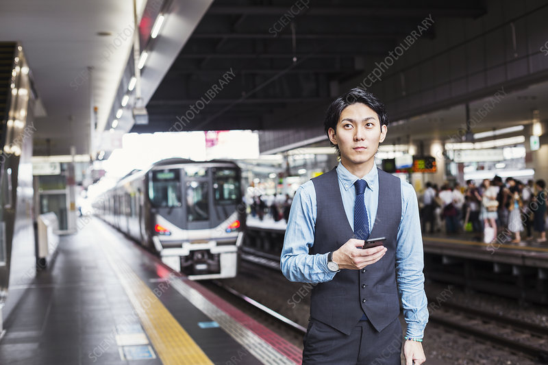 Businessman, train platform, mobile phone, looking at camera