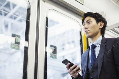 Businessman standing holding mobile phone
