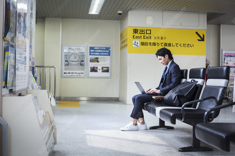 Businessman sitting at train station, working on laptop