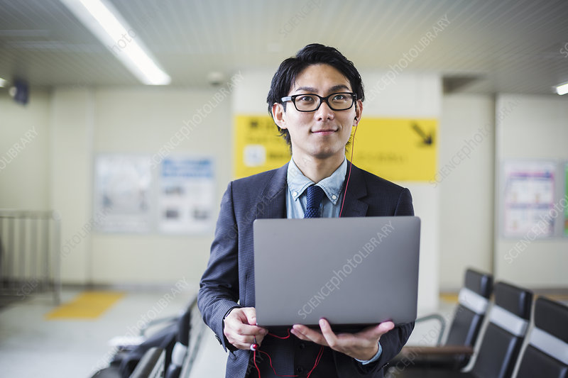 Businessman standing at train station, holding laptop