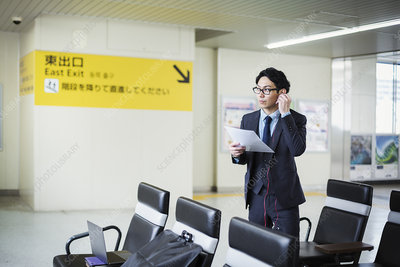 Businessman with headphones at train station, holding papers