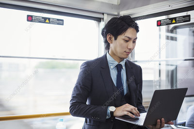 Businessman standing on a commuter train, holding laptop
