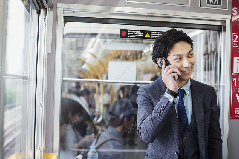 Businessman on commuter train, talking on mobile phone