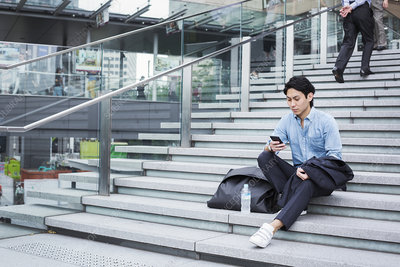 Businessman outdoors on steps, blue shirt, mobile phone
