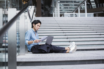 Businessman outdoors, steps, blue shirt, papers, laptop
