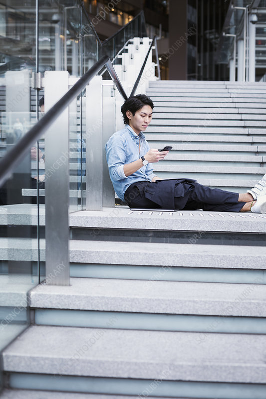 Businessman sitting on steps, blue shirt, mobile phone