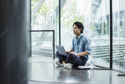 Businessman sitting on floor indoors, glass wall, laptop