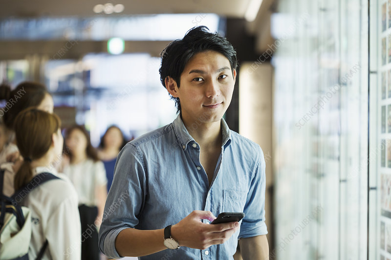 Businessman, blue shirt, mobile phone, looking at camera