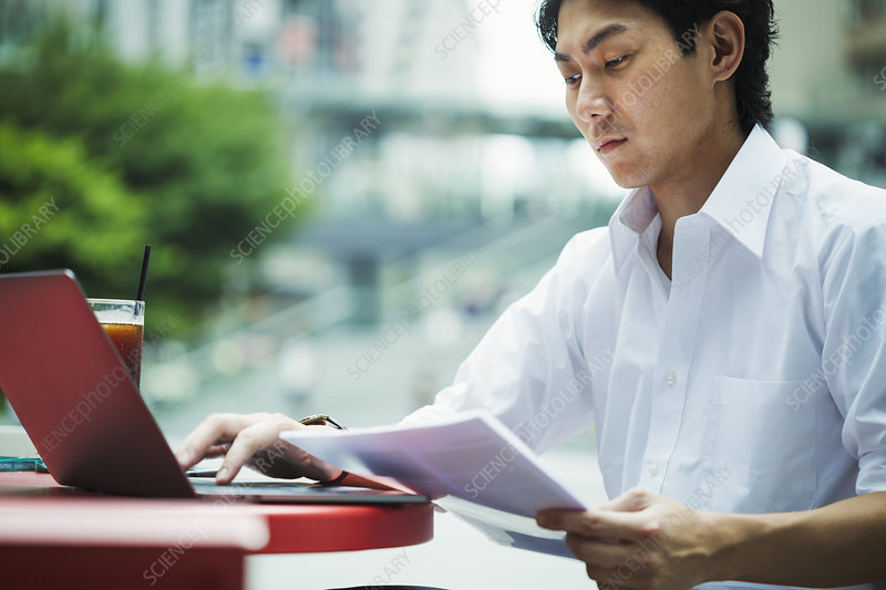 Businessman, outdoors, red table, holding papers, laptop