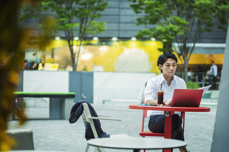 Businessman sitting outdoors at red table, working on laptop