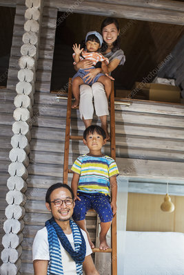 Family, man, woman, boy, girl, sitting on ladder, smiling