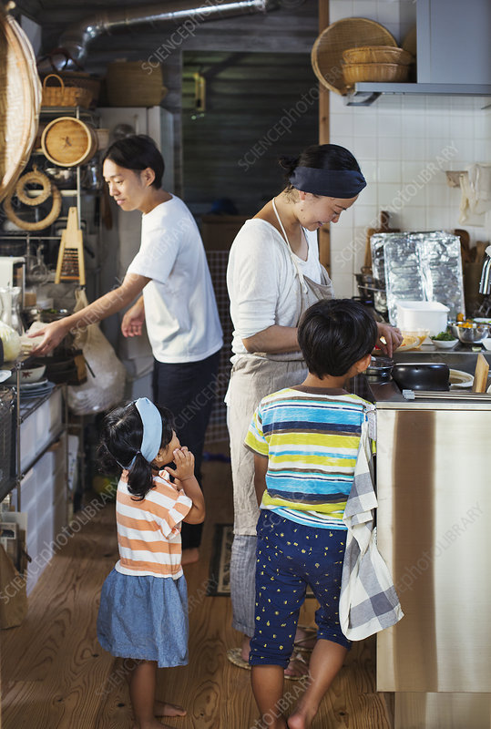Man, woman in apron, boy, young girl preparing food, kitchen