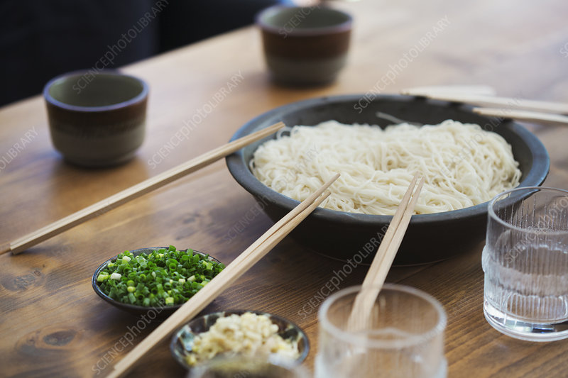 Close up, bowl, noodles, pairs of wooden chopsticks, table