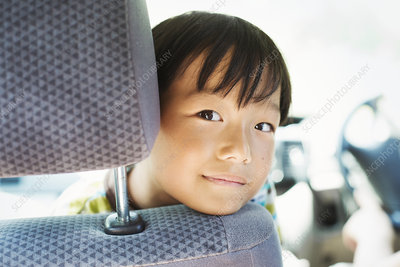 Boy sitting in a car, looking at camera