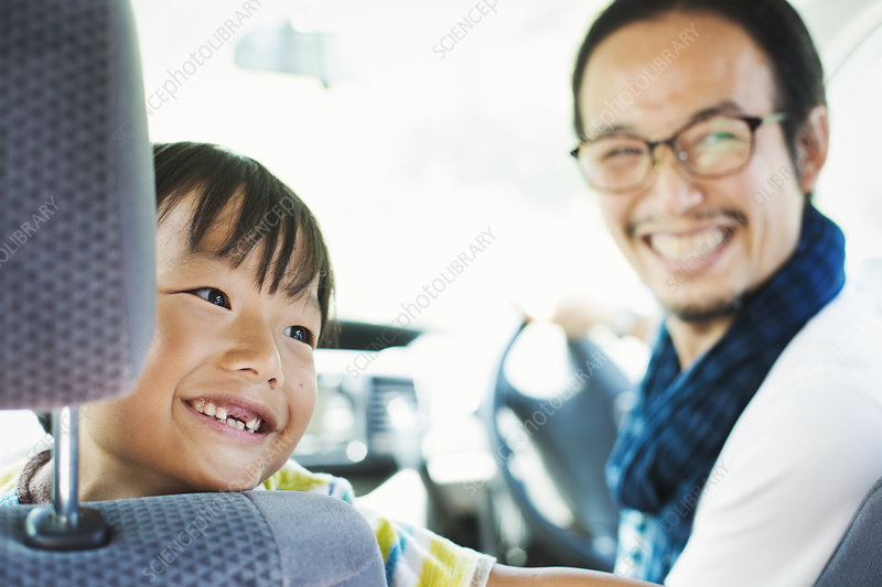 Man wearing glasses, boy sitting in a car, smiling at camera