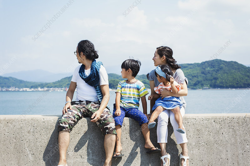 Family, man, boy, woman, girl on lap, on wall by ocean