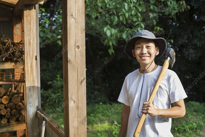 Smiling man in garden, hat, axe, looking at camera