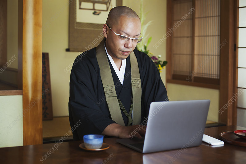 Buddhist monk at table indoors, black robe, laptop