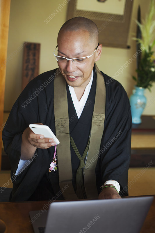Buddhist monk at table, black robe, laptop, mobile phone