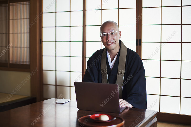 Smiling Buddhist monk at table, black robe, laptop, indoors