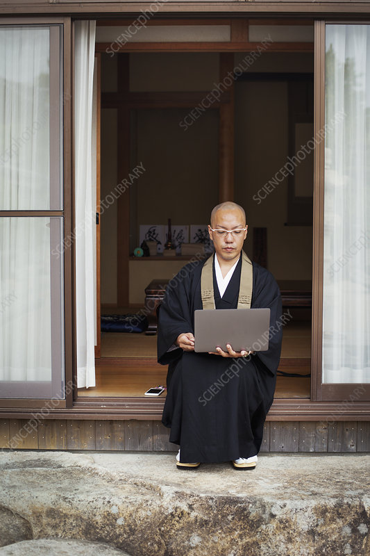 Buddhist monk siting by temple, black robe, laptop computer