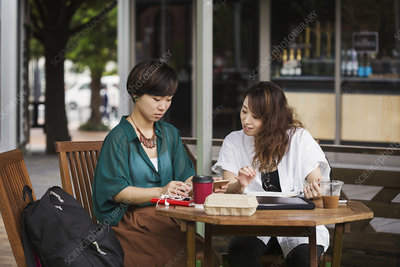 Two women at street caf table, looking at digital tablet