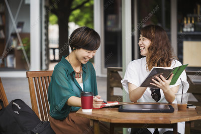 Two smiling women at street caf table, digital tablet