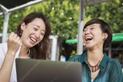 Two laughing women sitting, laptop, table in a street cafe