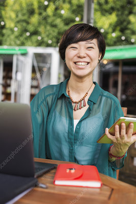 Woman smiling, street caf table, laptop, digital tablet