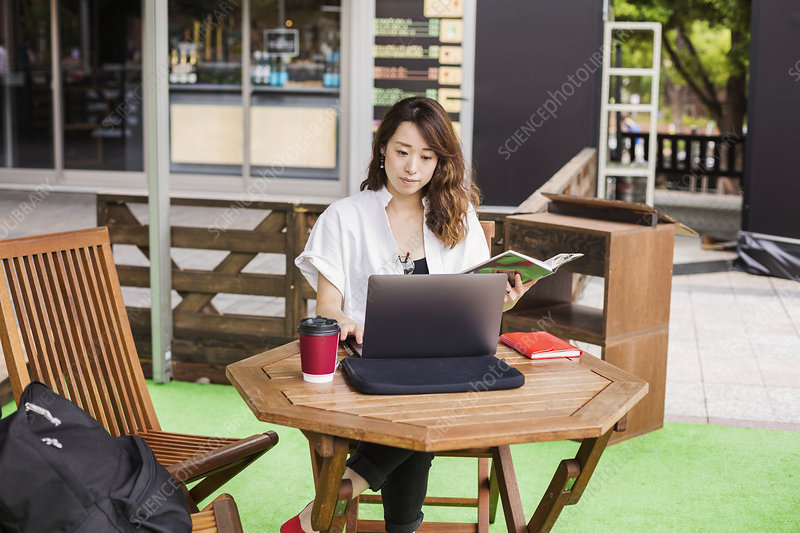 Woman working on laptop at table in a street caf