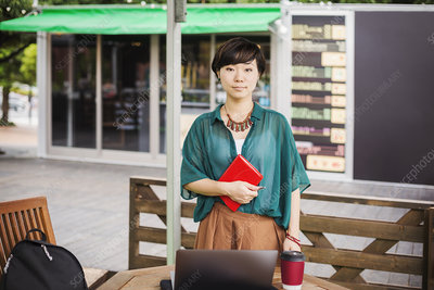 Woman standing outdoors at a street cafe, looking at camera