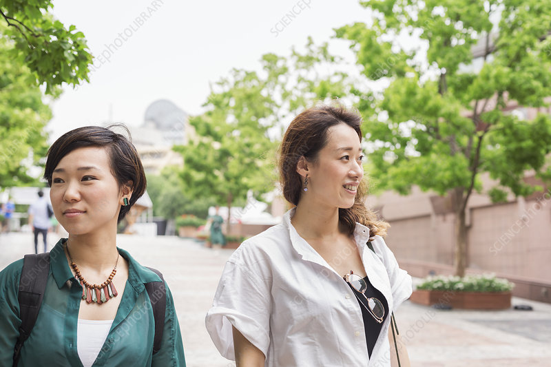 Two women walking along a street, smiling