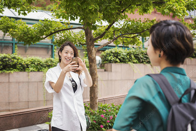 Two women outdoors, taking picture, mobile phone, smiling
