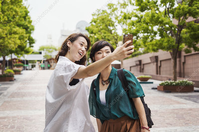 Two women outdoors, taking selfie, mobile phone, smiling